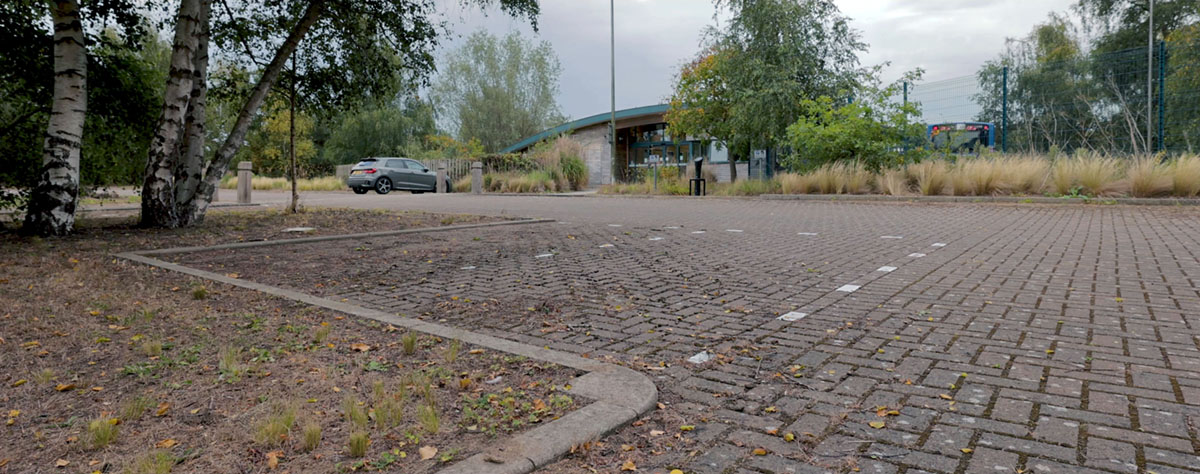 A photo showing Martlesham Park & Ride carpark with paving, trees and landscaping.